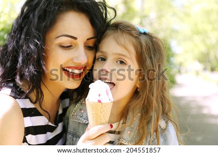 Happy mom and daughter in the green park with ice cream  - stock photo