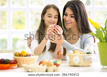 Happy mom and  daughter painting Easter eggs - stock photo