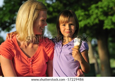 happy mom and daughter sharing an ice cream in the park - stock photo