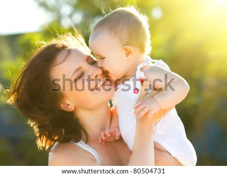 happy mom and daughter smiling at nature - stock photo