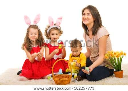 Happy mom and kids sitting on carpet with Easter basket and spring flowers - stock photo