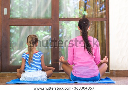 Happy mom and little girl doing yoga exercise on terrace outdoors - stock photo