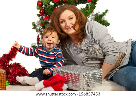 Happy mom and son celebrate first Christmas in front of Xmas tree - stock photo