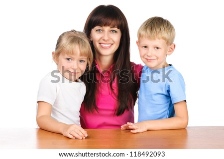 happy mom or young teacher sitting at table with two children isolated over white - stock photo