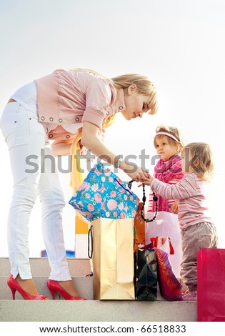 Happy mom with children and shopping on the street - stock photo
