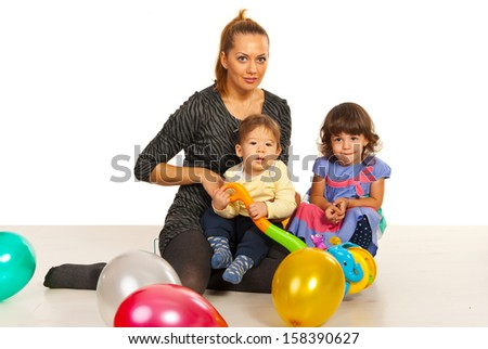 Happy mom with her kids sitting on floor with ballons - stock photo