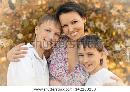 happy mom with her two sons rest on the nature - stock photo