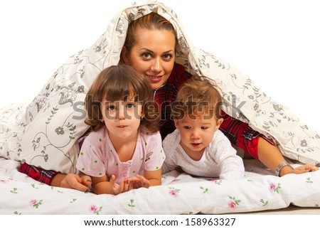 Happy mom with two kids in bed having fun - stock photo