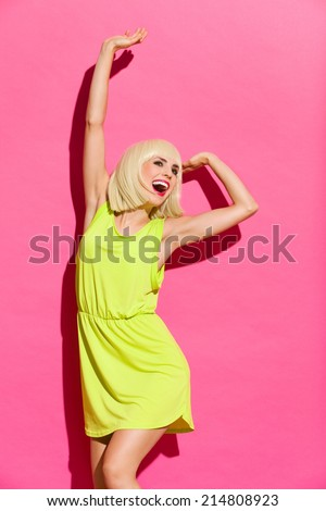 Happy monday morning. Sexy blond girl in lime dress stretching. Three quarter length studio shot on pink background. - stock photo