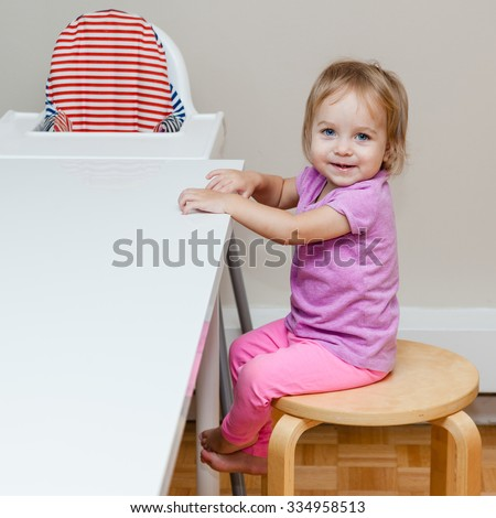 Happy 18 month old child sitting on the adult chair at dinner table instead of using his own baby high chair. Feeling like grown up. Kid looking straight to the camera. - stock photo
