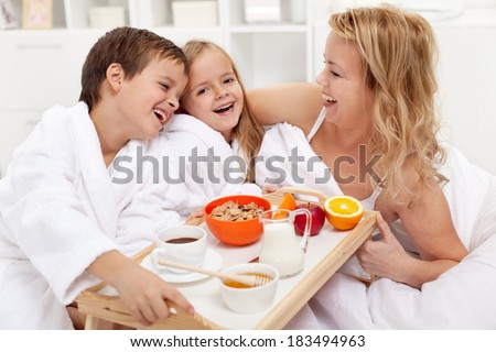 Happy morning - breakfast in bed for mom, kids pampering their mother - stock photo