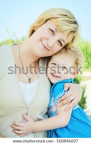 happy mother and adorable baby daughter posing outdoors. smiling family. beautiful blond woman and funny little girl in trendy wear. mother and daughter hugging in summer park - stock photo