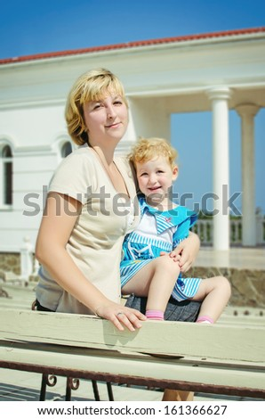 happy mother and adorable baby daughter posing outdoors. smiling family. beautiful blond woman and funny little girl in trendy wear. mother and daughter sitting on the wooden bench in summer park - stock photo