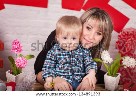 happy mother and adorable baby son smiling family beautiful woman and funny baby boy little lovely child in trendy wear. Cute toddler kid playing game with mother. smiling small baby infant in studio - stock photo