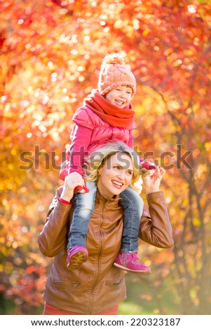 Happy mother and and smiling kid walking together outdoor in autumn or fall park. Child sitting on her mother's neck. - stock photo