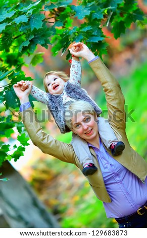 happy mother and baby girl having fun in colorful park - stock photo