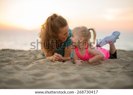 Happy mother and baby girl laying on beach in the evening - stock photo
