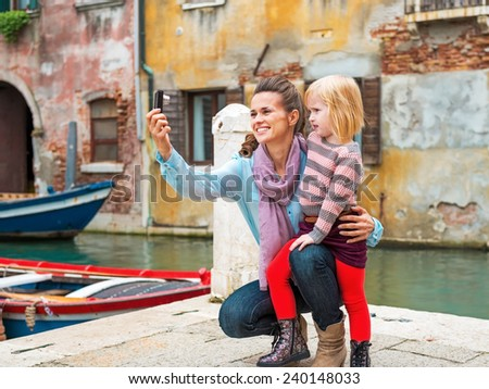 Happy mother and baby girl making selfie in venice, italy - stock photo
