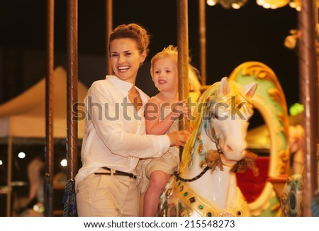 Happy mother and baby girl riding on carousel - stock photo