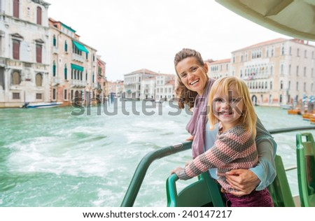 Happy mother and baby girl travel by venice water bus - stock photo