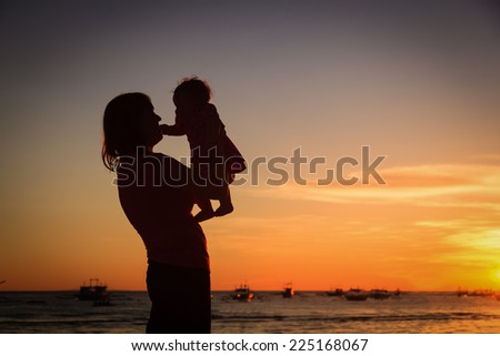 happy mother and baby having fun at sunset beach - stock photo