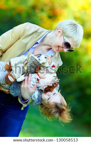 happy mother and baby having fun in colorful park - stock photo