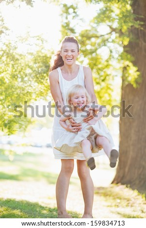 Happy mother and baby having fun outdoors - stock photo