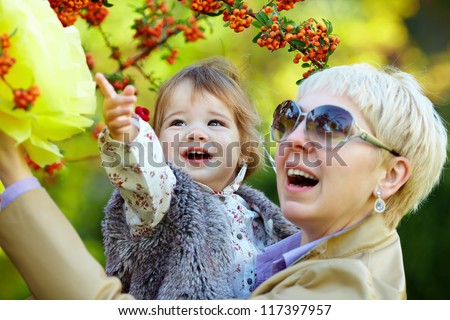 happy mother and baby in autumn park - stock photo