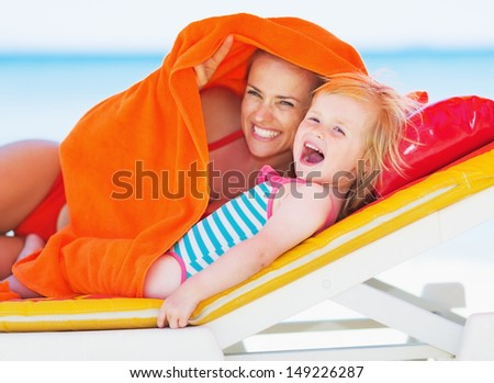 Happy mother and baby laying on chaise-longue and looking on copy space - stock photo