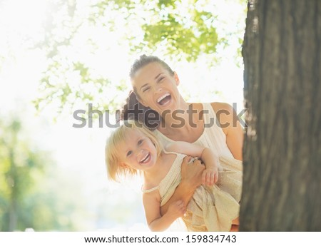 Happy mother and baby looking out from tree - stock photo
