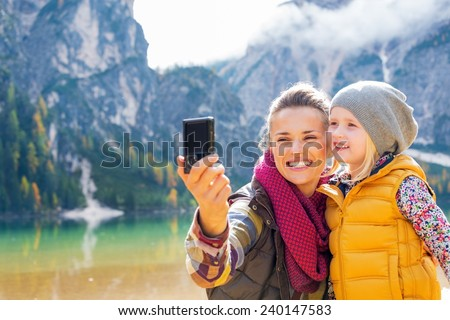 Happy mother and baby making selfie on lake braies in south tyrol, italy - stock photo