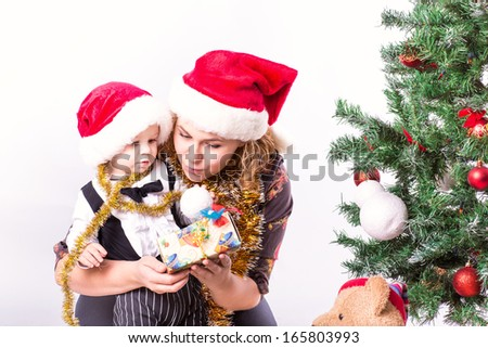 Happy mother and baby near Christmas tree in Santa's hat - stock photo