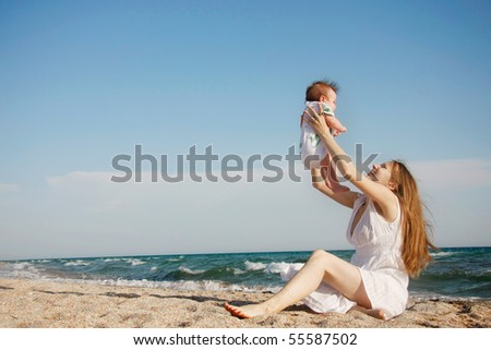 happy mother and baby on beach - stock photo