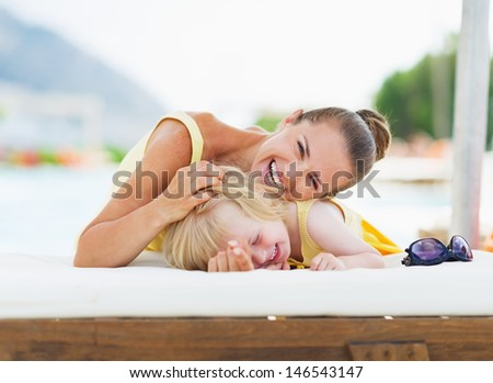 Happy mother and baby playing at poolside - stock photo