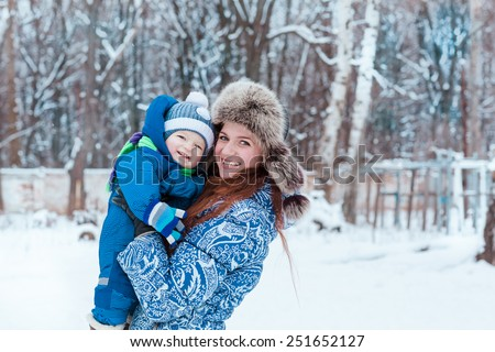 Happy mother and baby playing on snow in winter park - stock photo