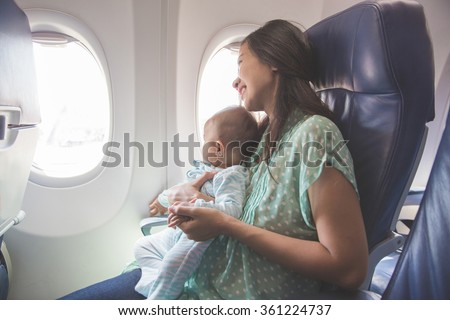 Happy mother and baby sitting together in airplane cabin near window - stock photo