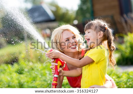 Happy mother and child daughter water in domestic garden - stock photo