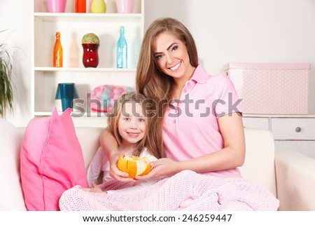 Happy mother and child eating fruit - stock photo