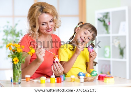 Happy mother and child girl preparing to Easter holiday and with brush coloring eggs - stock photo