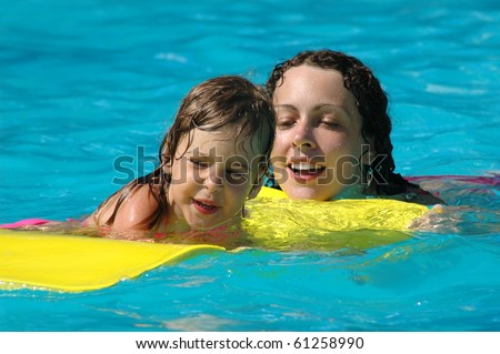 Happy mother and child have fun in pool - stock photo