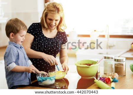 Happy mother and child in kitchen preparing cookies - stock photo