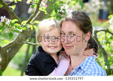 Happy mother and child in the garden - stock photo