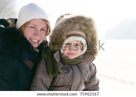 Happy mother and child in winter time - stock photo
