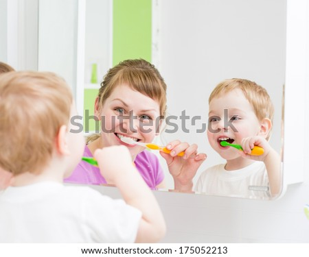 Happy mother and child teeth brushing  in bathroom front of mirror - stock photo