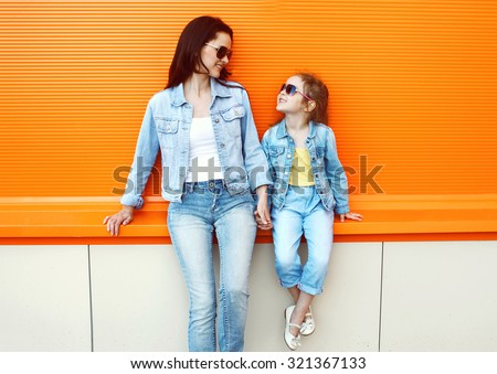 Happy mother and child wearing a jeans clothes in city - stock photo