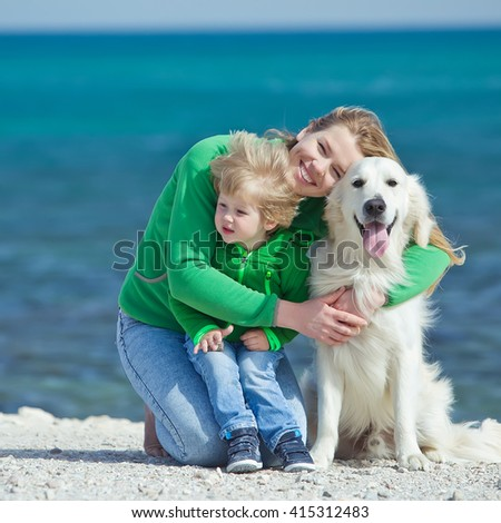 Happy mother and child with Golden Retriever dog  - stock photo
