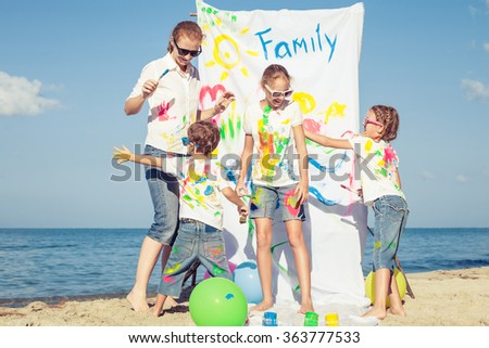 Happy mother and children playing with paint on the beach at the day time. Concept of friendly family. - stock photo
