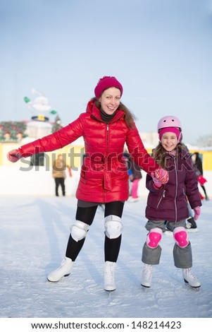 Happy mother and daughter are skating at the outdoor skating rink in winter - stock photo