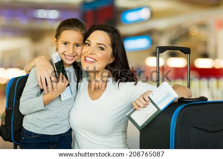 happy mother and daughter at airport travelling together - stock photo