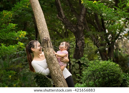 Happy mother and daughter/baby playing joyfully around a tree in - stock photo